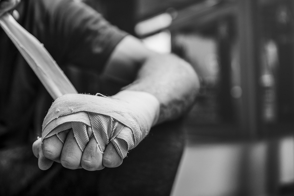 A boxer wraps his hand in preparation for a fight.