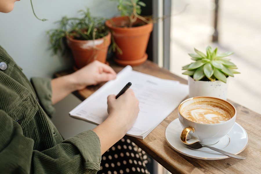 Woman sit at office surround with green plants, coffee and taking notes.