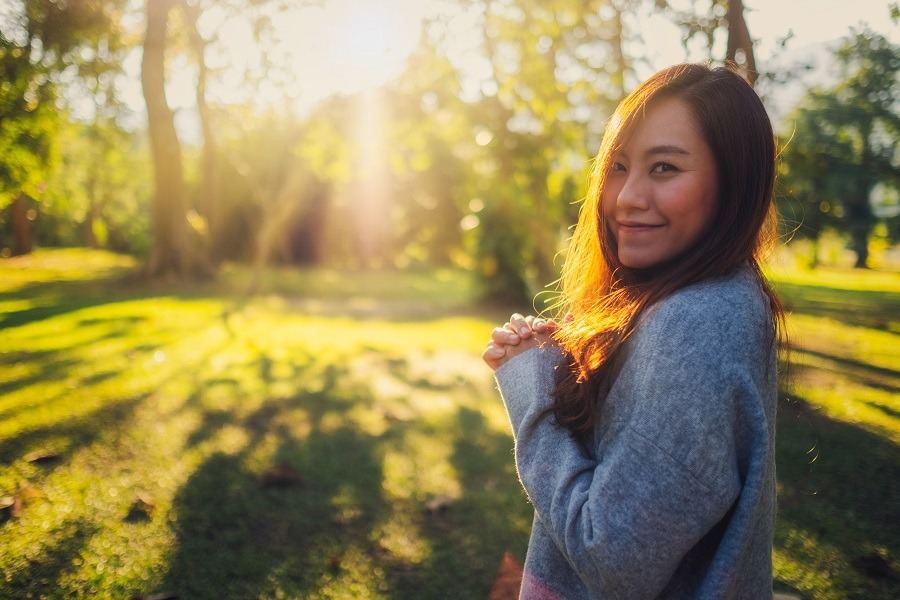 Beautiful asian woman smiling, standing at a park in bright sunlight.