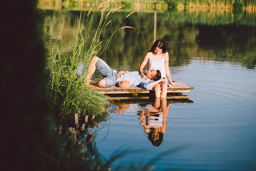 Young love couple gazing at each other man on girl's lap at the lake in summer.