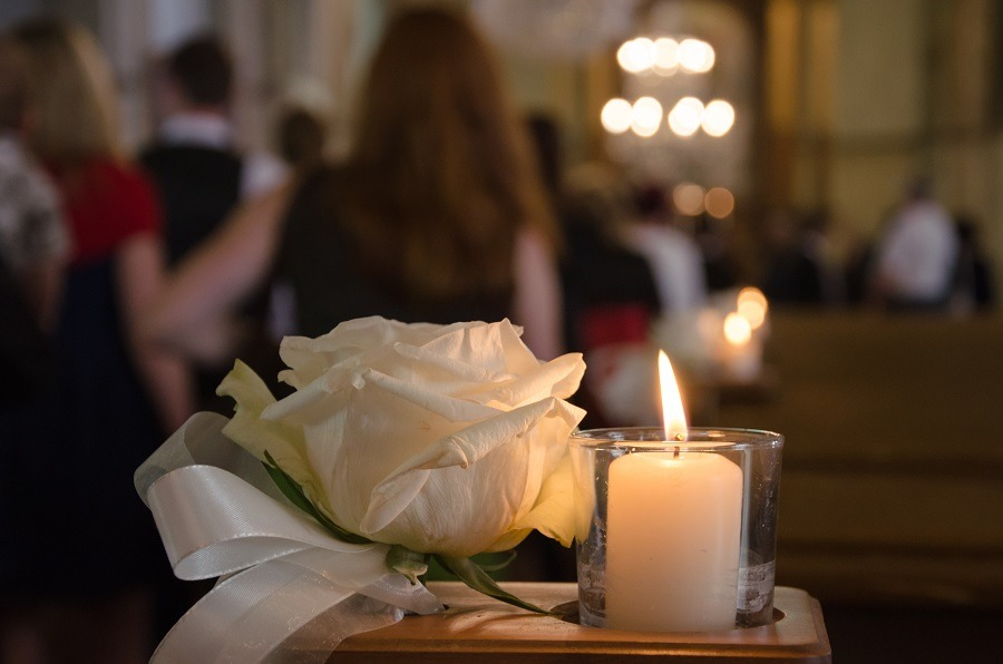 White rose and candle in a church, people in the background.