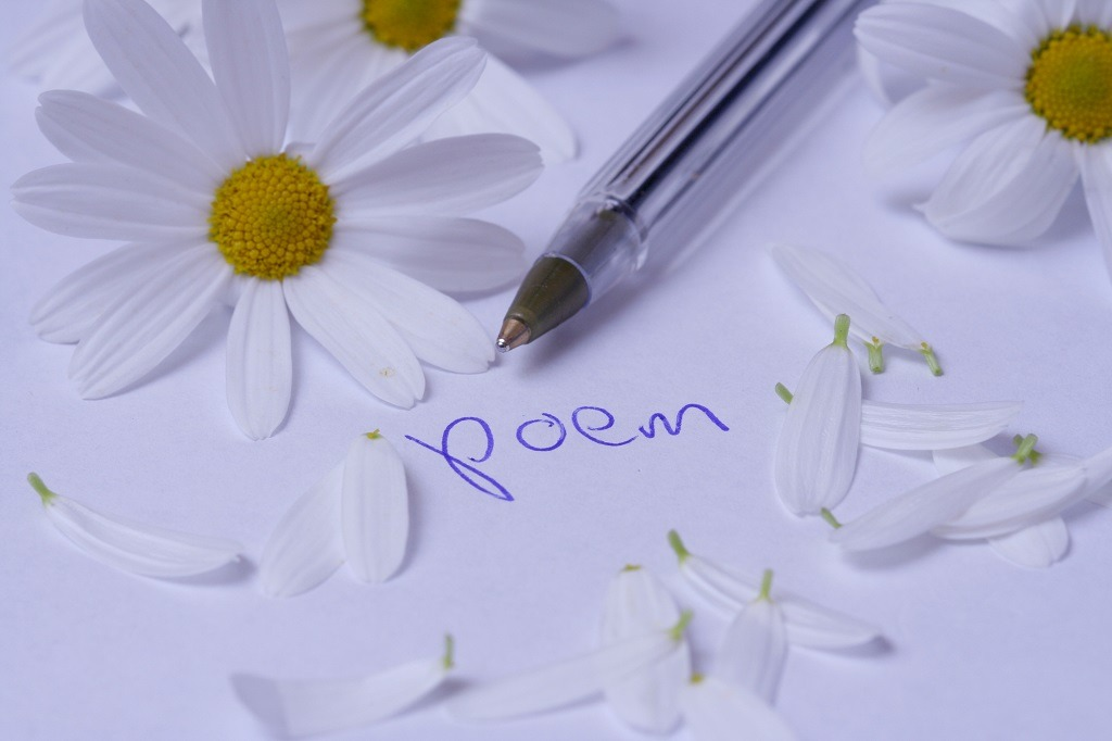 Poem word written on white paper with flower petals.