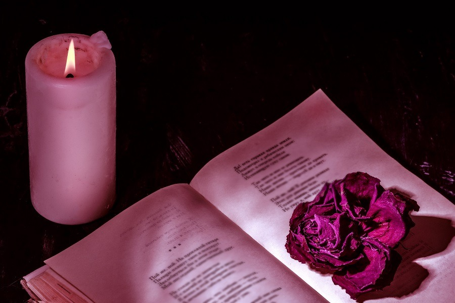 An open book of poems with a candle and a dried pink rose on top of the page.