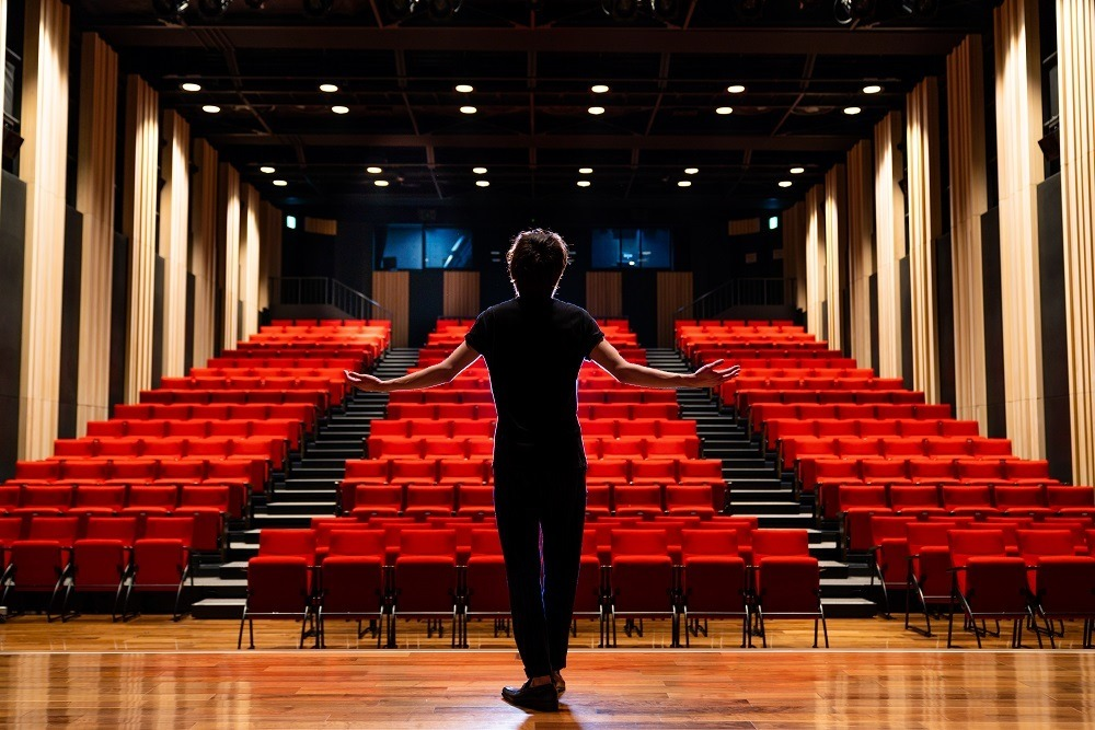 A male actor rehearsing on stage in an empty theater.