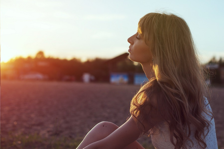Young woman on beach under sunset light, eyes closed in deep thought.
