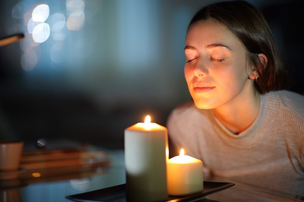 A woman with eyes closed, smelling a lighted candle.