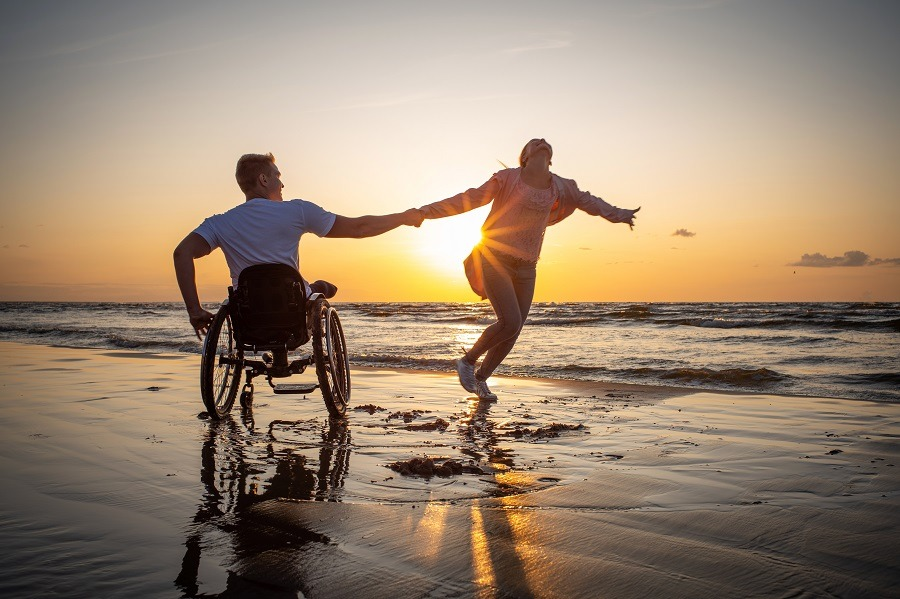 Handicapped man in wheelchair and his girlfriend holding hands on a beach at sunset.