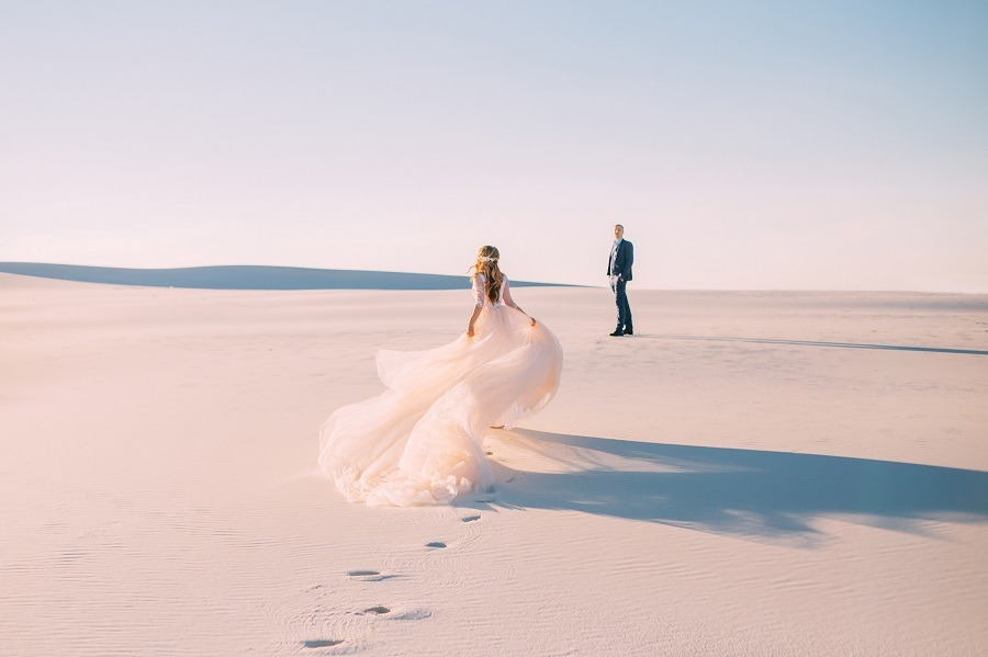 A woman in beautiful white gown runs to meet her man in the desert at sunset.