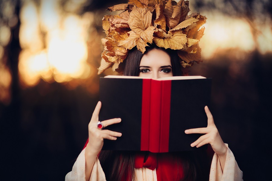 Woman storyteller with autumn leaves crown, book covering her face except the eyes.