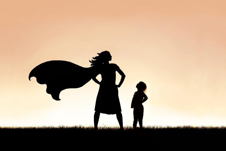 Silhouette of strong beautiful caped super hero woman.