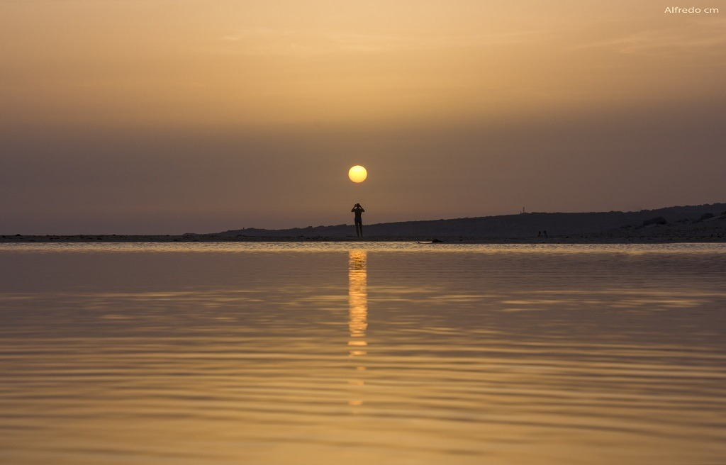 Landscape of a sunset in the sea, the sky and the sea are tinged with romantic undertone orange colors.