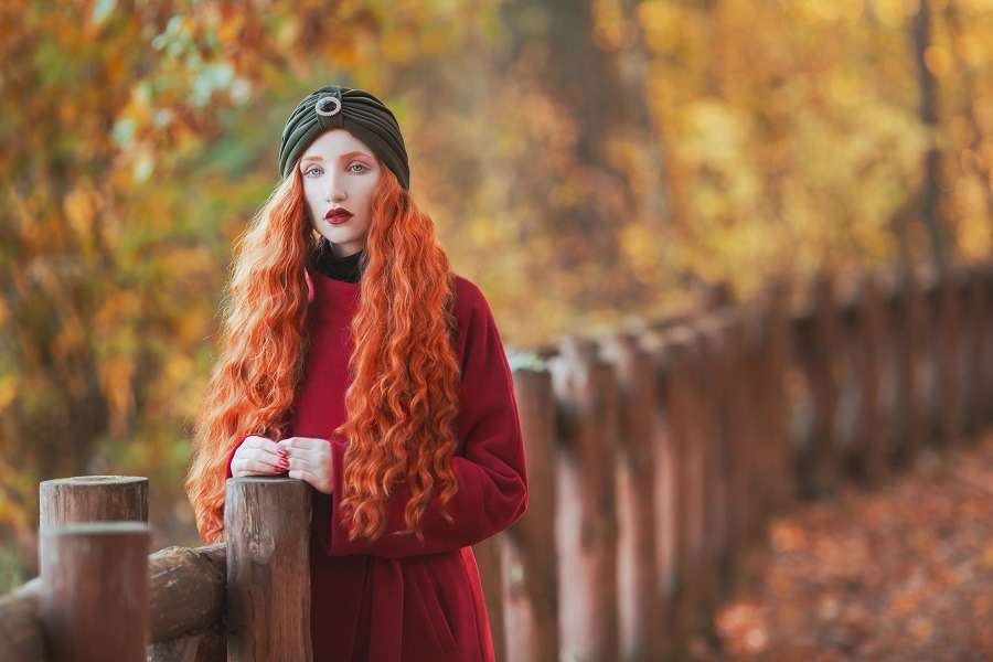 Beautiful long-haired redhead lady on picturesque autumn background.
