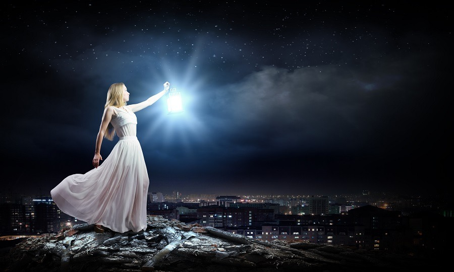 Beautiful fairy in white in the city at night time.