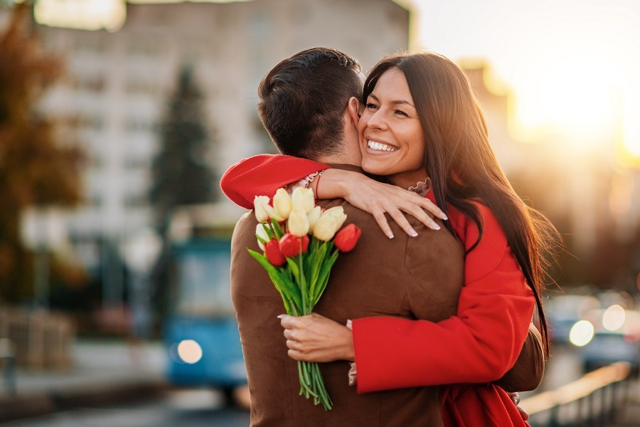 Happy woman holds beautiful bouquet in one hand, hugs partner on back view.