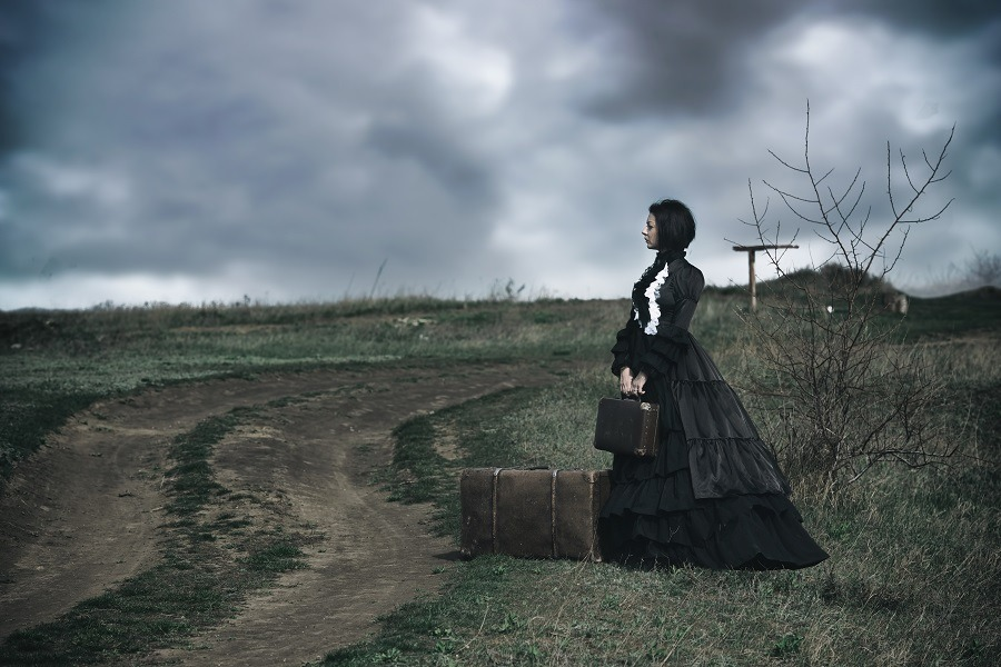 A victorian lady in black standing alone on the road with her luggage.