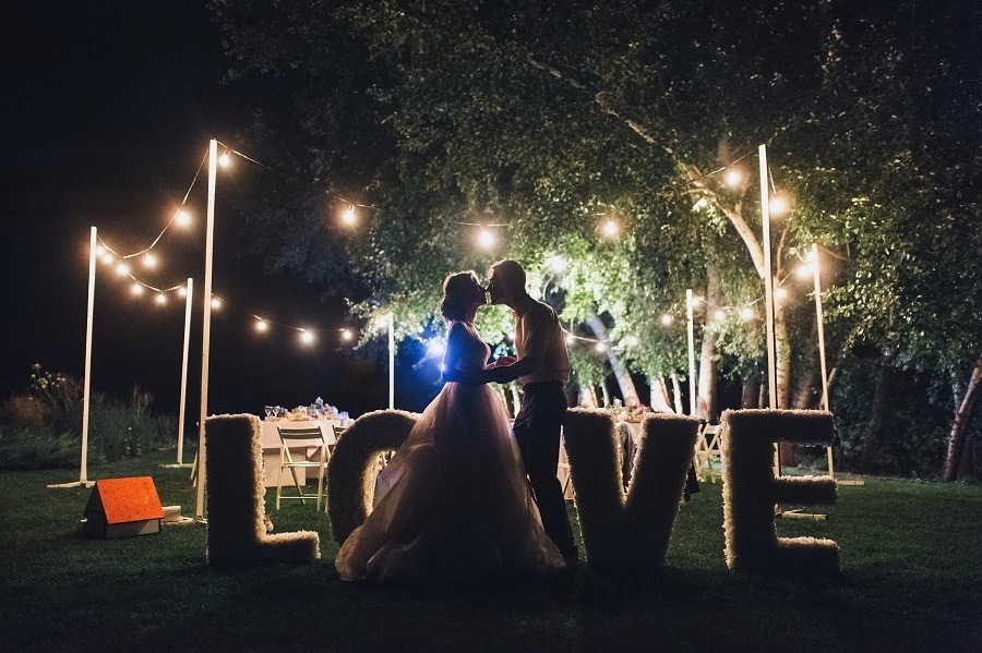 Beautiful newlyweds kiss tenderly at a wedding party with lamps.