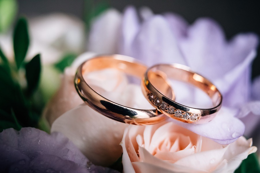 Wedding rings on bouquet of peach roses.