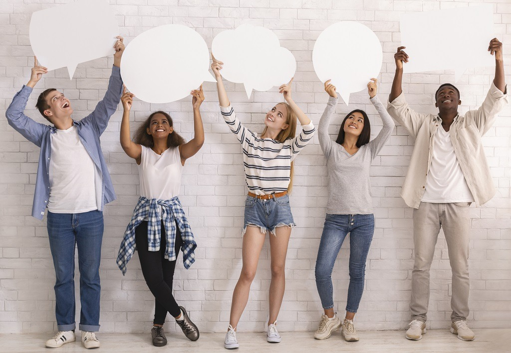 Smiling multicultural teenagers looking at empty speech bubbles above.