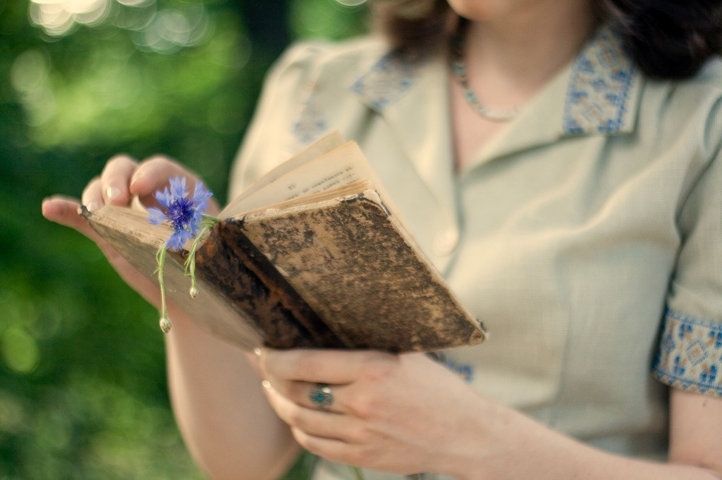 A young girl in a vintage dress holding old book.