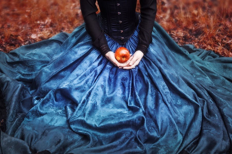 Mysterious Snow White holds a ripe apple on her lap.