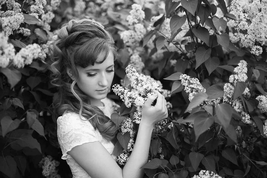 Elegant and fragile woman in lilac garden.