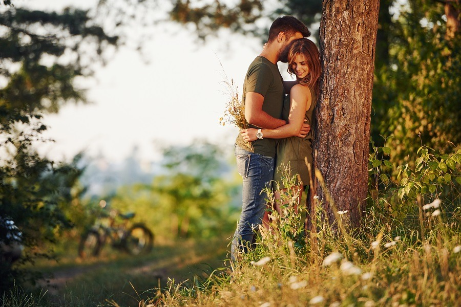 Beautiful young couple leaning on the tree having a good time in the forest at daytime.