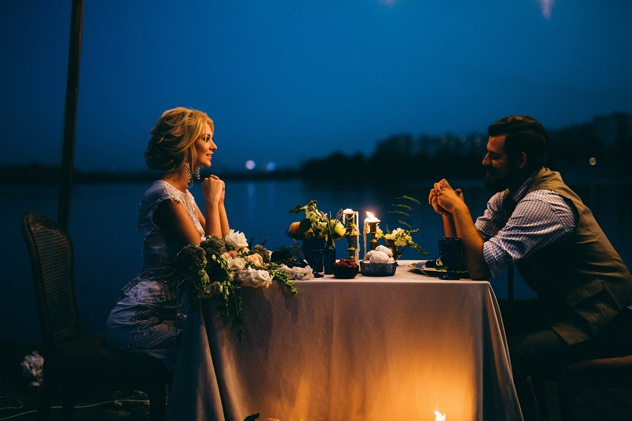 Sweet couple in love on a romantic dinner by the river at night.