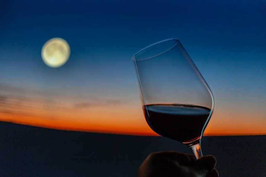 Raised glass of wine with yellow moon in the background.