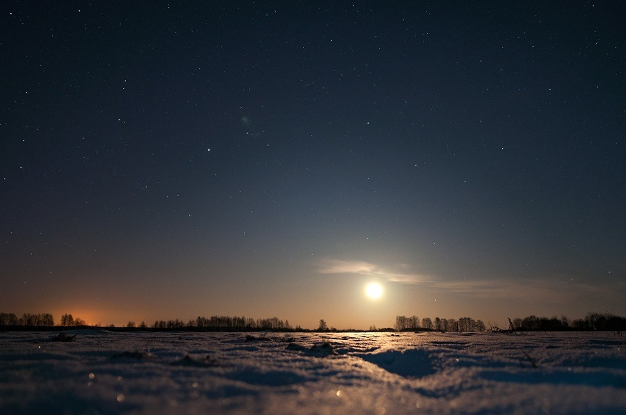 Moon rising over the field, winter night.