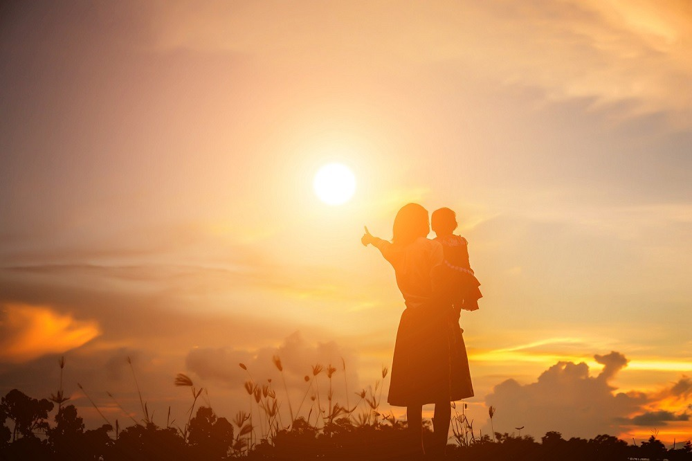 A silhouette of a child in the arms of his loving mother watching the sunset.