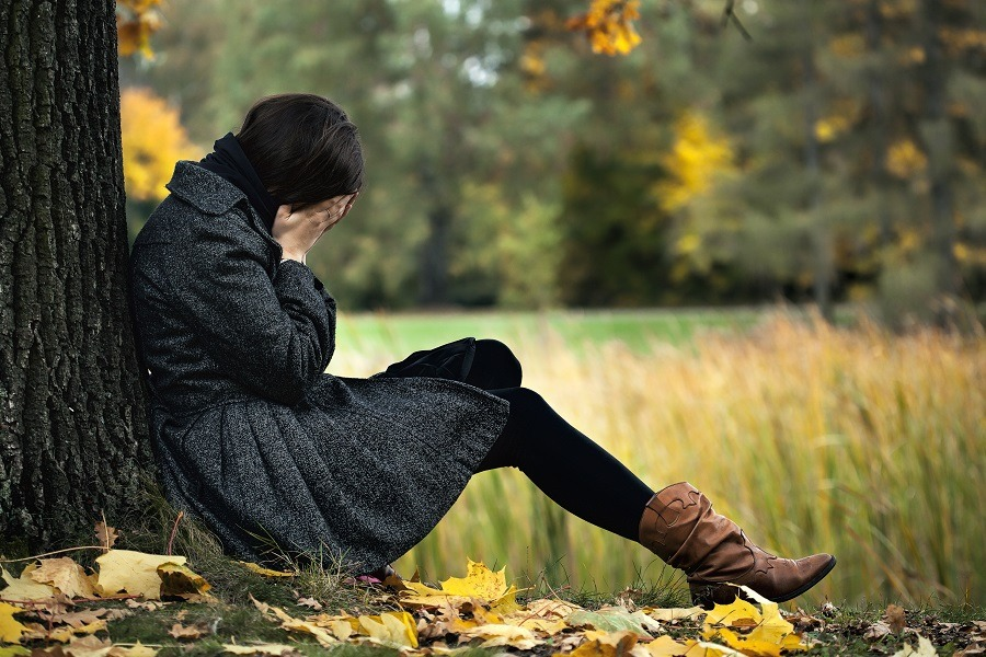 Woman hands covering face crying seated on the ground back to the tree in autumn.