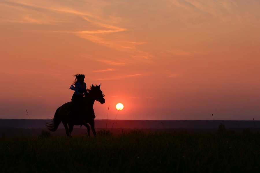 Woman horse riding with red rising sun on horizon.