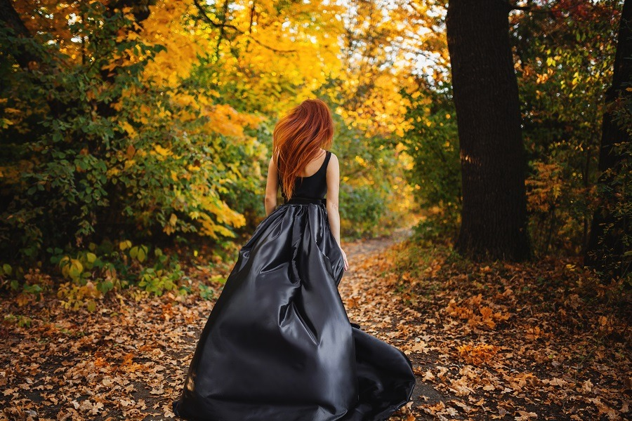 Woman long hair running to orange forest in autumn.