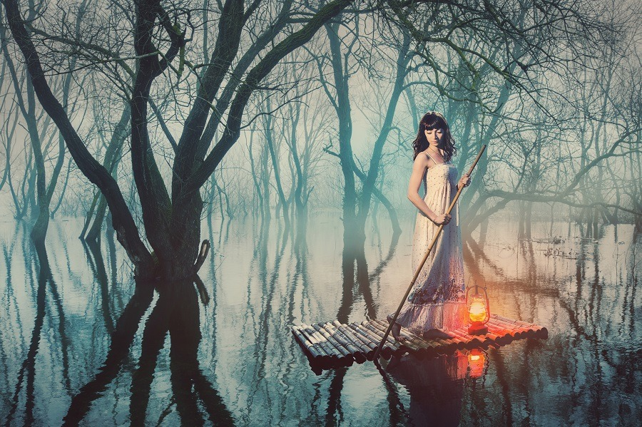 Stunning woman on a raft with a lantern floating on a pond in a misty forest.