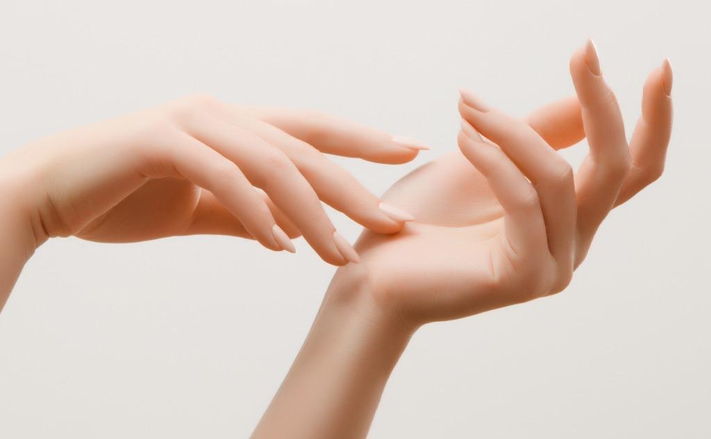 Closeup image of beautiful woman's hands with light pink manicure on the nails