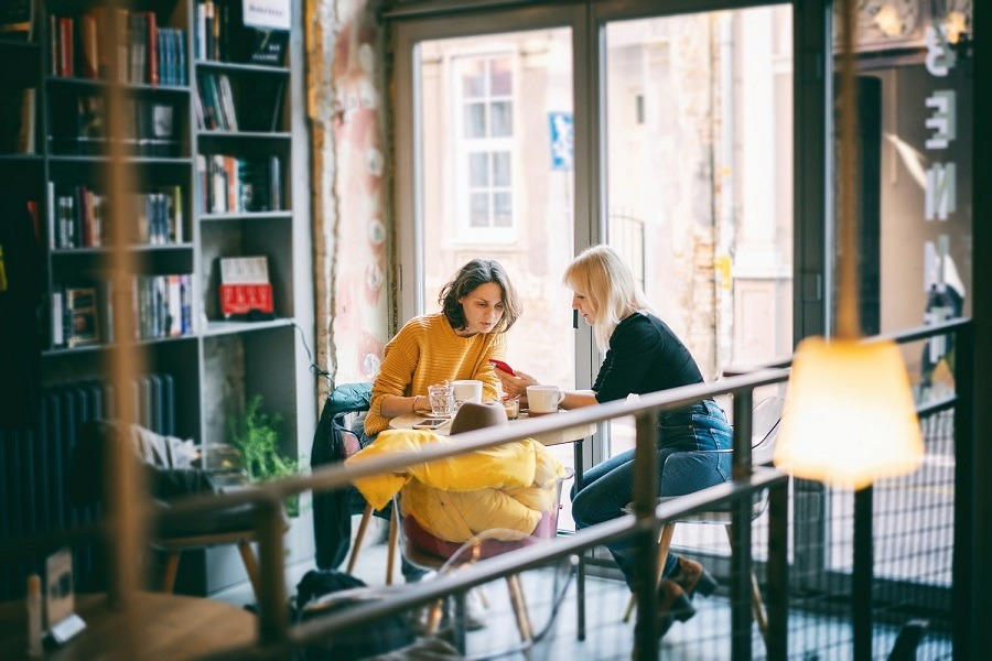 Two women friends sitting in a café conversing over coffee.