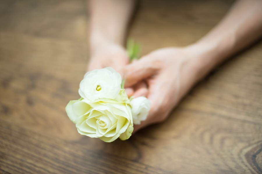 Hands on a wooden table holding yellow roses.
