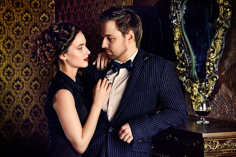 Beautiful man and woman in elegant evening vintage clothes standing close with intense desire for each other.