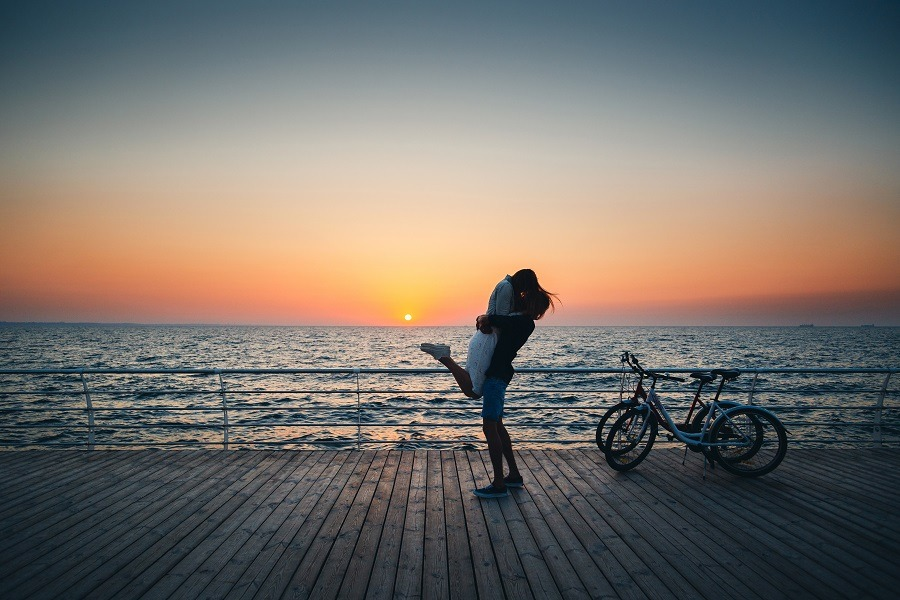 Man holding his girlfriend, kissing at the beach at sunrise sky at wooden deck in summer time.