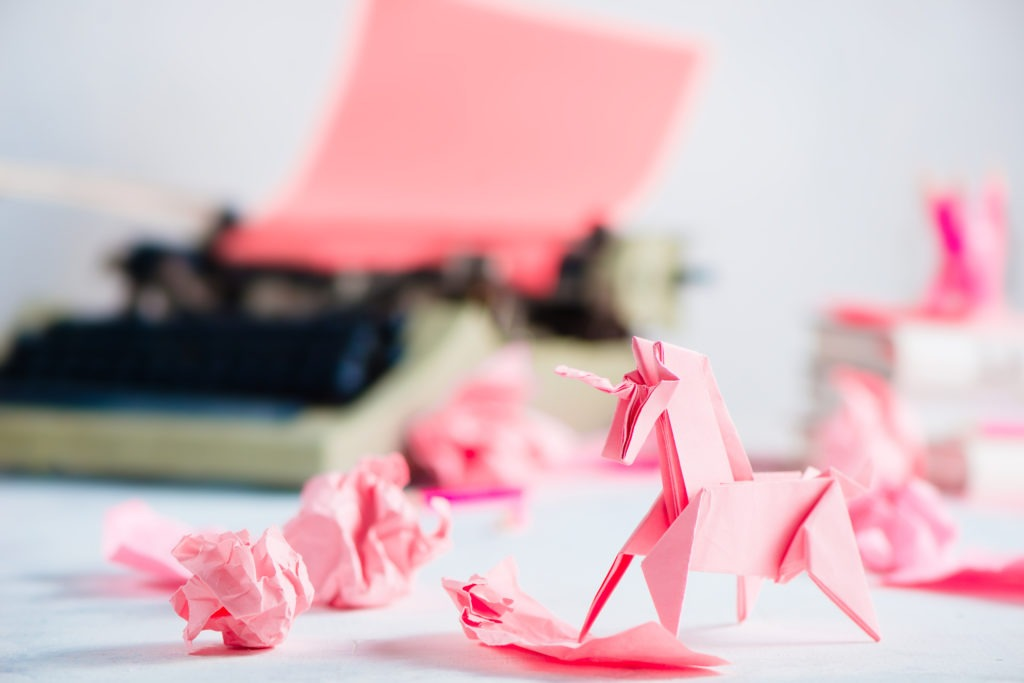 Pink origami unicorn with crumpled paper balls and a typewriter. Creative process in writing.