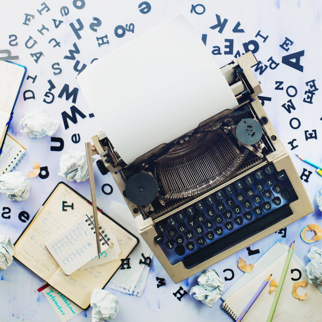 Modern typewriter surrounded by letters.