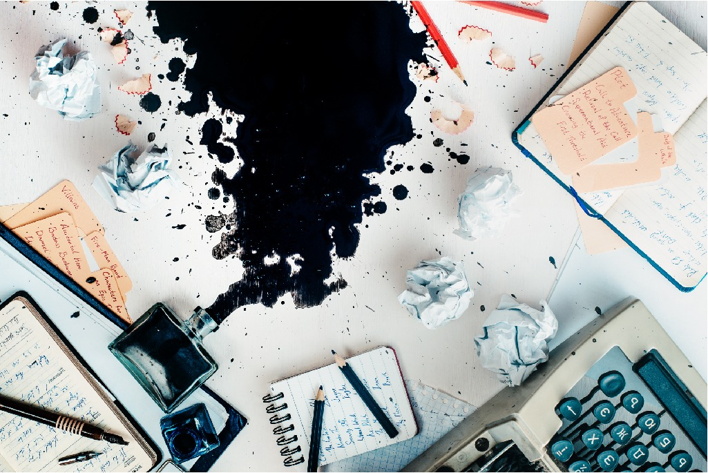 Writer workplace with spilled ink, stationery and a typewriter. Crumpled paper balls with pencils on a white wooden background, creative writing concept. Flat lay with copy space.